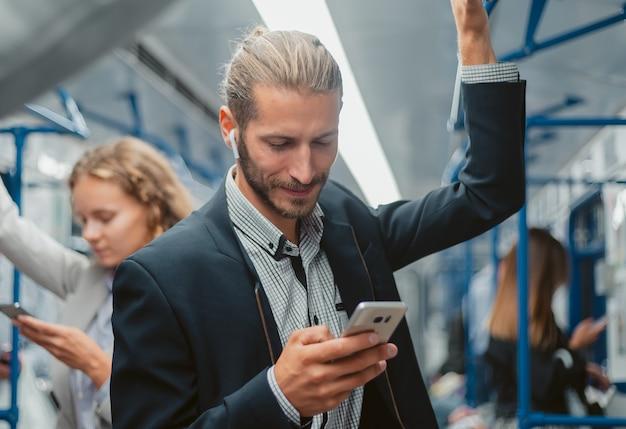 그의 스마트 폰에서 메시지를 읽고 웃는 승객. 사람과 기술.