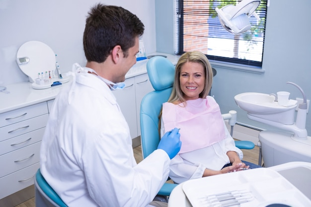 Smiling patient discussing with dentist