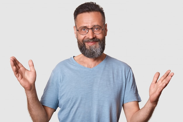 Smiling peaceful man rises his arms, greets somebody, looks pleased, wearing trendy spectacles and blue casual t shirt, spends spare time with pleasure. people, emotions and communication concept.