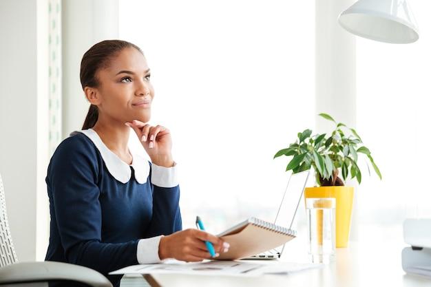 オフィスの職場に座ってドレスを着て物思いにふけるアフリカのビジネス女性の笑顔。