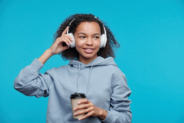 Smiling pensive black teenage girl listening to music in wireless headphones and drinking coffee against blue background