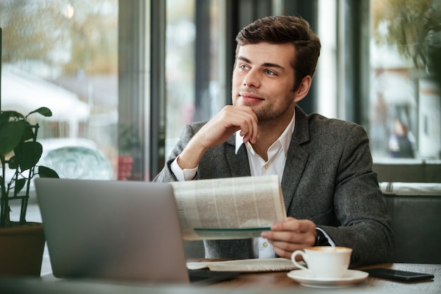 Smiling pensive businessman sitting by the table in cafe with laptop computer and newspaper while looking away