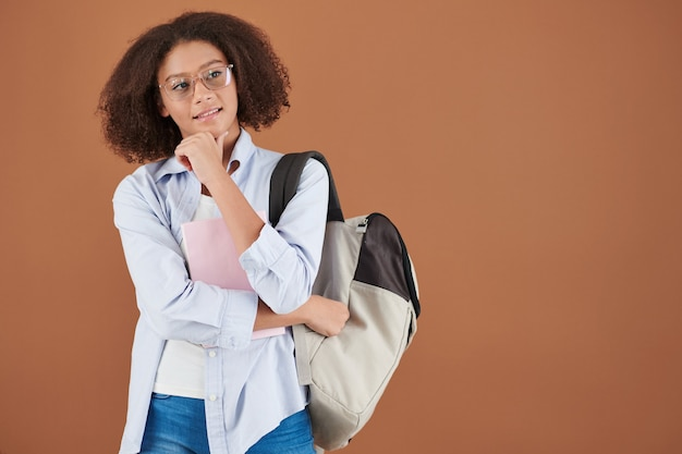 Smiling pensive high school girl in glasses and blue shirt standing with satchel and rubbing chin while looking away