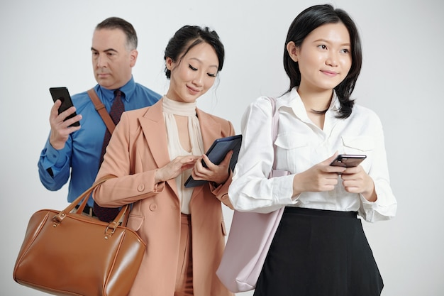 스마트폰을 들고 웃고 있는 생각에 잠긴 젊은 여성 사업가, 뒤에 서서 문자 메시지와 이메일에 답하는 동료들