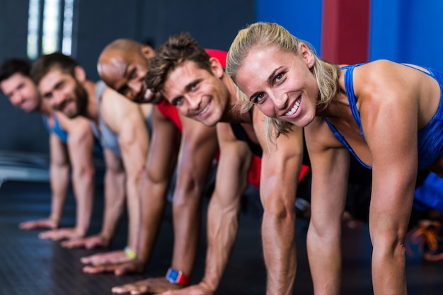 Smiling people doing push-ups in gym