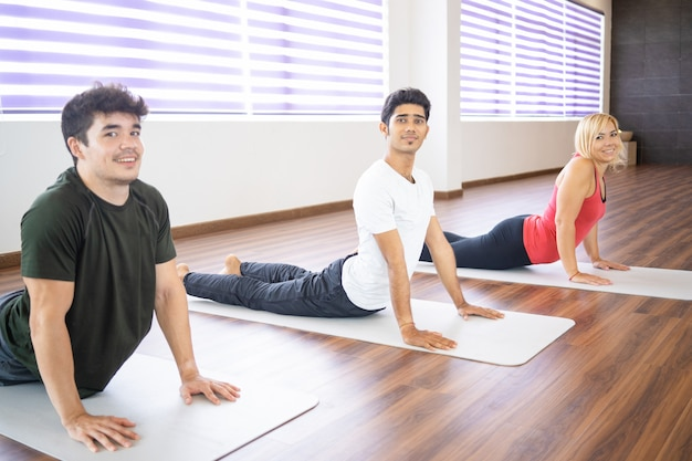 Smiling people doing upward facing dog pose at class