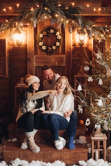 Smiling people sitting on wooden porch in front of door with xmas wreath