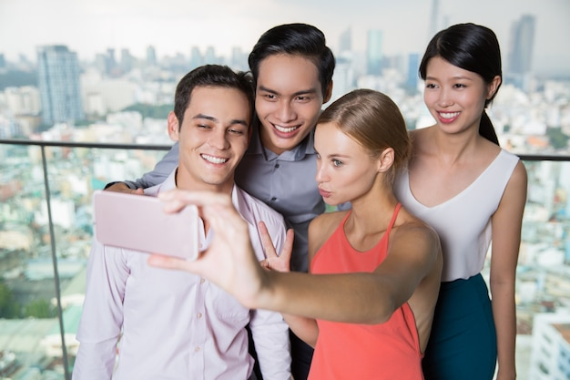 Smiling people taking selfie photo with smartphone