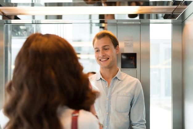 Smiling people talking in an elevator