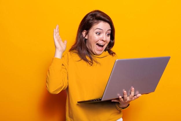 ノートパソコンのビデオ通話で手を振って笑顔の人