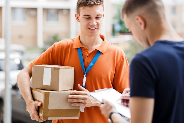 A smiling person wearing an orange t-shirt and a name tag is delivering a parcel to a client, who is putting his signature on the receipt. friendly worker, high quality delivery service.