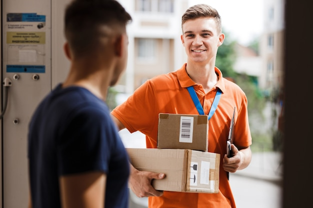 A smiling person wearing an orange t-shirt and a name tag is delivering parcels to a client. friendly worker, high quality delivery service.