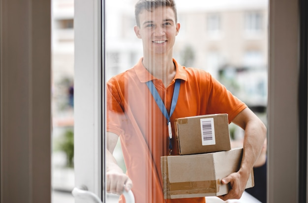 A smiling person wearing an orange t-shirt and a name tag is standing behind the glass door and holding a door handle and parcels for the client. friendly worker, high quality delivery service.
