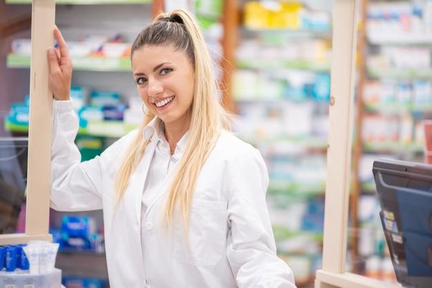 Smiling pharmacist inside her pharmacy