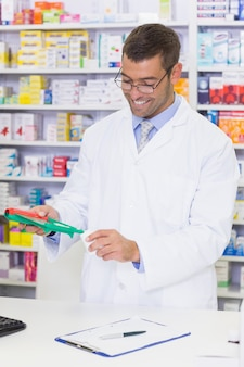 Smiling pharmacist mixing a medicine