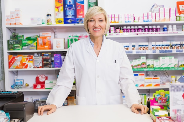 Smiling pharmacist posing behind the counter