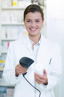 Усмехаясь аптекарь используя сканер штрих-кода на бутылке медицины в аптеке