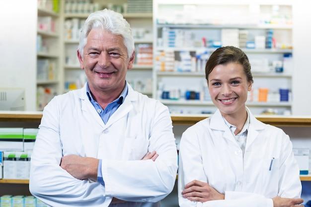 Улыбающиеся фармацевты, стоя с оружием, пересекли в аптеке