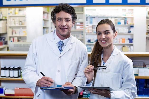 Улыбающиеся фармацевты с буфером обмена и цифровой планшет в аптеке