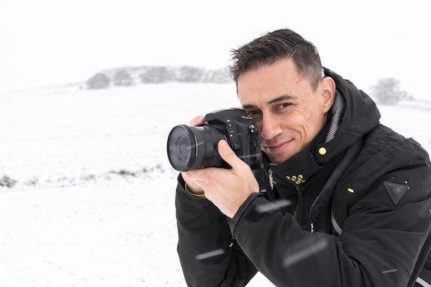 Улыбающийся фотограф делает снимки в снежном пейзаже в холодный зимний день