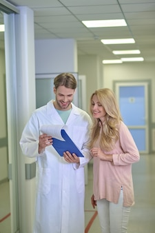 Smiling physician and a joyful woman scrutinizing a document