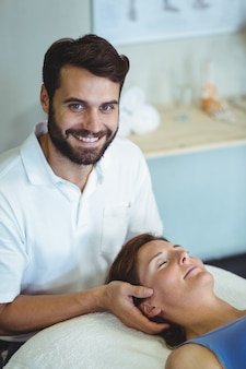 Smiling physiotherapist giving head massage to a woman