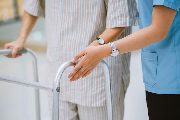 휠체어에 행복 노인 환자를 돌보는 물리 요법가 미소