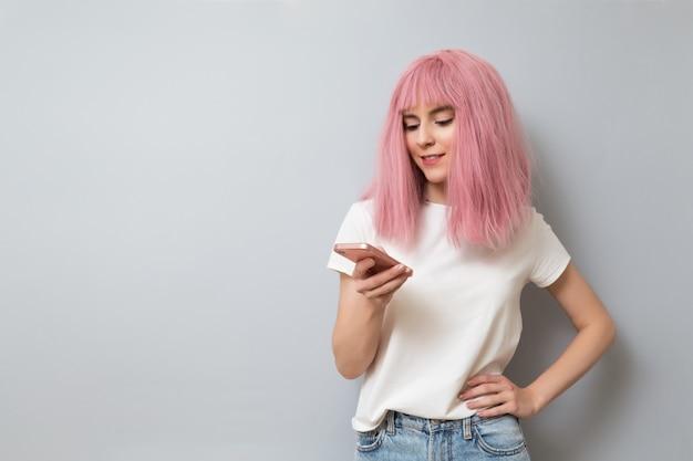 スマートフォンでメッセージを書いているピンクの髪の少女の笑顔。オンライン学習、インターネットサーフィン、オンラインコミュニケーションの概念