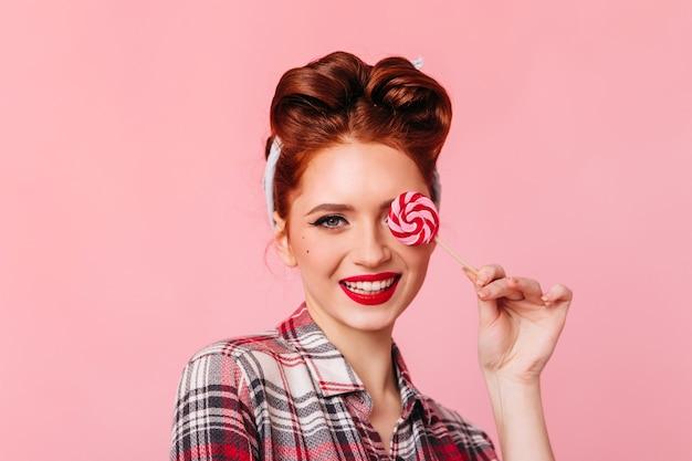 赤いロリポップを食べるピンナップガールの笑顔。ピンクのスペースで隔離の市松模様のシャツを着た女性の正面図。