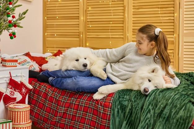 大きな白いふわふわサモエド犬を抱き締める遊び心のあるかわいい女の子の笑顔