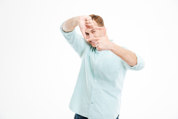 Улыбающийся игривый молодой человек, делающий кадр руками