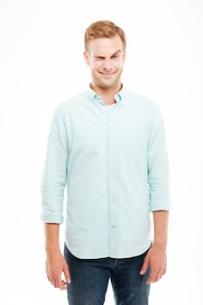 変な顔をして白い壁にウインクする遊び心のある若い男の笑顔