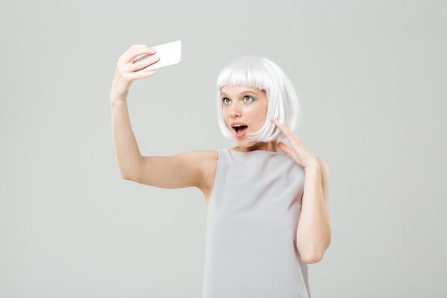 Smiling playful young woman making selfie using smartphone