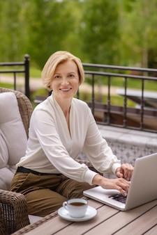 Улыбающаяся приятная блондинка средних лет удаленная работница сидит за деревянным столом и печатает на своем ноутбуке