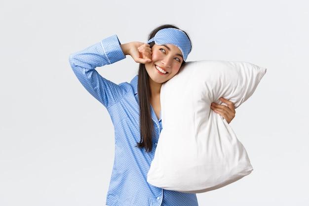 Улыбающаяся довольная азиатка в спальной маске и пижаме лежит в постели и обнимает подушку, растягивая ...