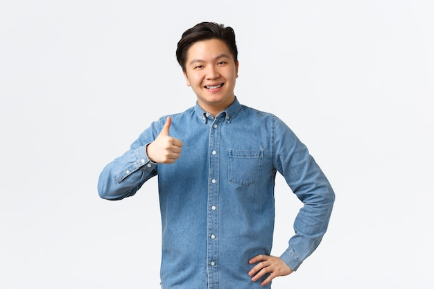 Smiling pleased asian male student with braces, showing thumbs-up, recommend product or service with excellent quality, like and approve idea. man nod in approval, agree with person, white background.