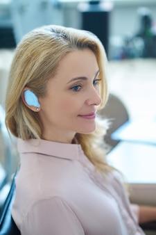 医者のオフィスに座っている耳に挿入されたデバイスで笑顔の満足している美しいブロンドの女性