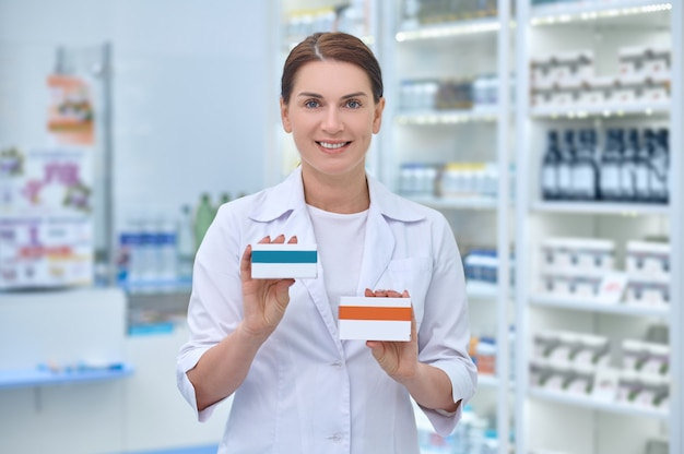 Smiling pleased beautiful female pharmaceutist holding two carton boxes with medicines in front of her