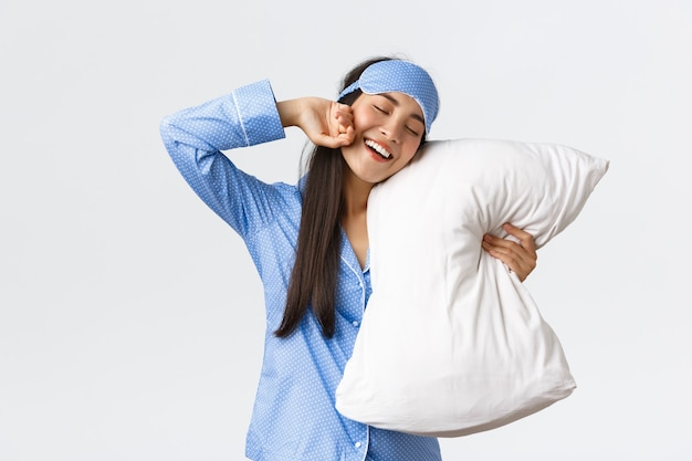 Smiling pleased cute asian girl in blue pyjama and sleeping mask, hugging pillow and stretching hands delighted as finally going bed, want sleep or waking up in morning, white background