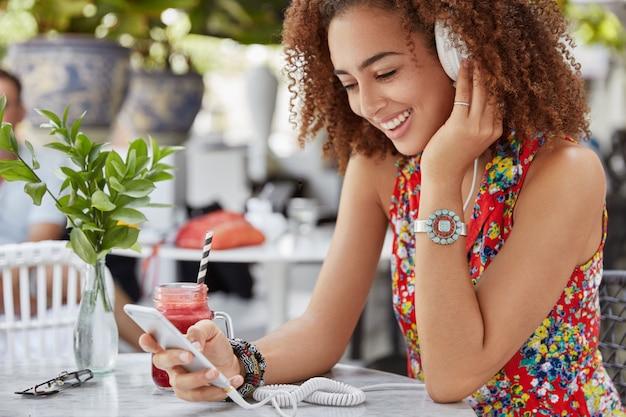 笑顔の喜んでいる暗い肌の女性モデルは屋外カフェで余暇を過ごし、ヘッドフォンでお気に入りの音楽を聴くための近代的な技術を使用しています