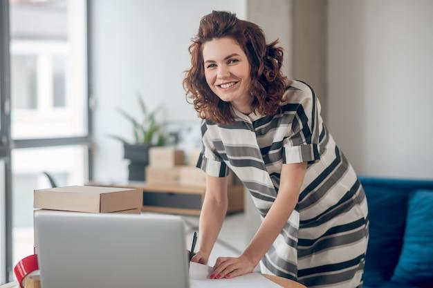 그녀의 손에 볼펜을 들고 웃고 있는 기뻐하는 직원이 앞을 바라보는 사무실 책상 위에 기대어 있다