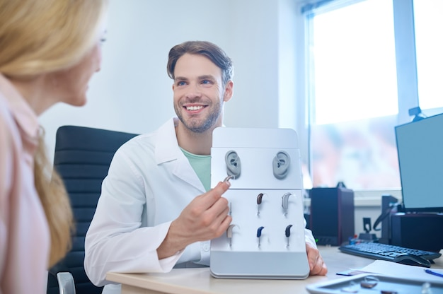 Smiling pleased handsome male audiologist showing a diversity of hearing devices to a blonde woman