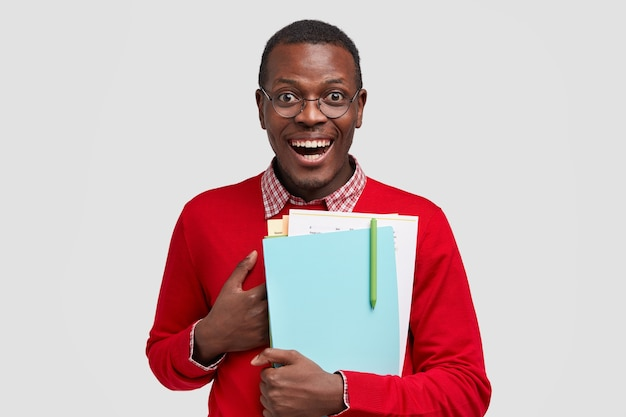 Smiling pleased male scientific worker keeps hand on chest, carries papers and notebook with pen, cant believe in his success, has joyful facial expression, wears round glasses