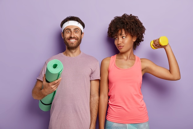 Smiling pleased man poses with fitness mat, wears purple t shirt and headband, lovely sporty woman looks at husband, trains biceps with weight, stand shoulder to shoulder indoor. aerobics and people