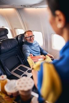Улыбающийся довольный мужчина, получающий еду в авиакомпании