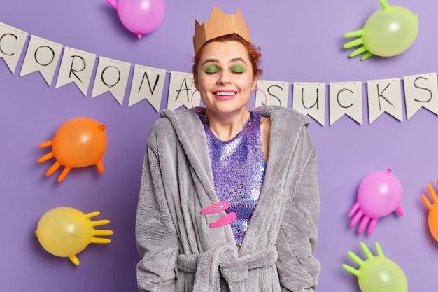 Улыбающаяся довольная женщина с зеленым ярким макияжем закрывает глаза от удовольствия, мечтает, что коронавирус уходит, одетая в повседневный халат, вокруг цветных шаров над пурпурной стеной