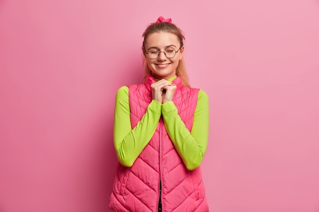 La giovane donna europea soddisfatta sorridente tiene le mani premute insieme e chiude gli occhi con piacere Foto Gratuite