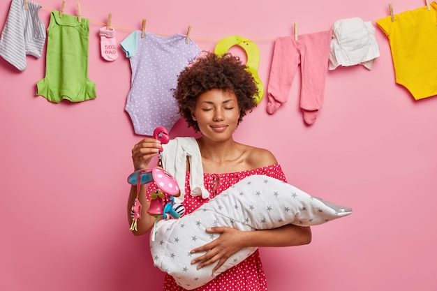 Smiling pleased young mother holds newborn child on hands, nurses little baby with mobile toy, enjoys calmness while newborn sleeping, poses against pink wall with kids clothes on rope