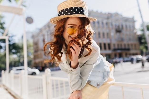 通りに立っているサングラスをかけた笑顔の若い女性。ロマンチックな生姜の女の子の屋外の肖像画は麦わら帽子とデニムジャケットを着ています。