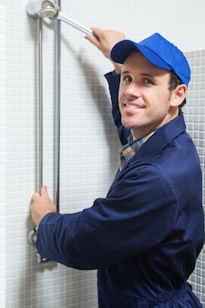 Smiling plumber repairing shower head